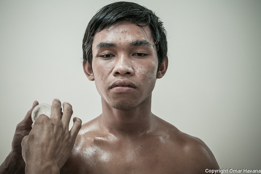 SIEM REAP, CAMBODIA. A Kun Khmer fighter is treated with cream moments before his fight at the new Siem Reap arena in Cambodia. Pradal Serey or Kun Khmer -free fighting- is an unarmed martial art from Cambodia. Compared to other forms of Southeast Asian kickboxing, Kun Khmer emphasises more elusive and shifty fighting stances. The Cambodian style tends to utilise more elbows than that of other regions. Evidence shows that a style resembling pradal serey existed in the 9th century, leading the Khmer to believe all Southeast Asian forms of kickboxing started with the early Mon-Khmer people. They maintain that Pradal Serey has influenced much of the basis of Muay Thai. During the Khmer Rouge genocide, traditional martial arts were banned and many boxers were executed or worked to death, which nearly caused the death of pradal serey. Nowadays, Kun Khmer is making a strong comeback in Cambodia, with fighters attempting to market their style of boxing at the same caliber of Muay Thai. Photography: ©Omar Havana
