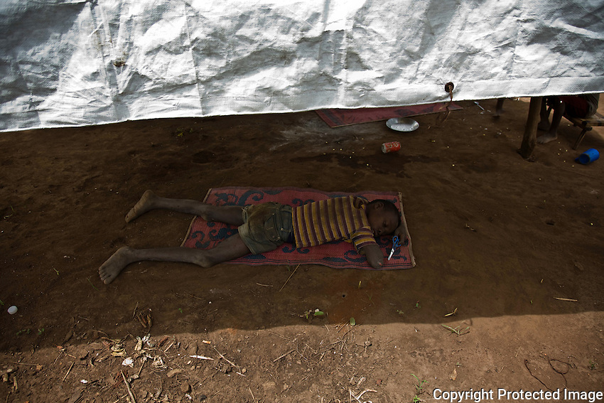 A child sleeping in Makpandu refugee camp,  44 km from Yambio, South Sudan.. The camp was set up for  refugees fleeing LRA attacks in Congo. Many other congolese refugees have found shelter amoung fellow Zande  families in towns and villages along the Congo Sudan border.