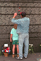 Father and son 40 and 9 placing poppy at Vietnam Wall on Memorial Day.  St Paul  Minnesota USA