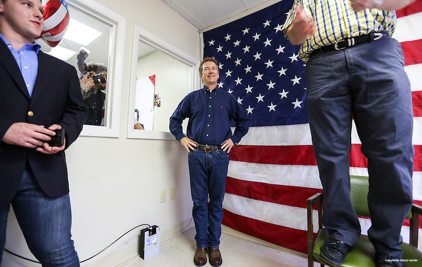 Presidential hopeful Rand Paul, left, listens as as NH Senator Andy Sanborn, standing on a chair, makes opening remarks commemorating the opening of Paul's campaign office in Manchester, N.H.,  Friday, June 5, 2015. (AP Photo/Cheryl Senter)