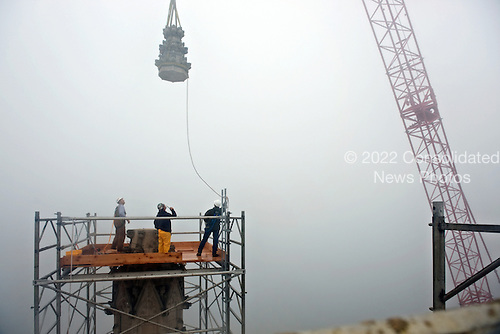 (From L-R) Against the foggy backdrop head stone mason Joe Alonso, Dave McAllister and Andy Uhl watch as the damaged upper portions of the southeast grand pinnacle, is hoisted by a crane from atop the central tower of the Washington National Cathedral, in Washington, D.C., on Thursday, October 13, 2011. The Cathedral's central tower pinnacles were damaged by the magnitude 5.8 earthquake that struck the East Coast on August 23. The damaged portions of pinnacles are being removed to make the pinnacles and central tower stable until the stonework can be repaired and put back in place.  .Credit: Nikki Kahn / Pool via CNP