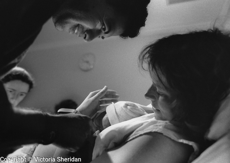 New parents smile and look over their newborn baby moments after birth. (Photo/Victoria Sheridan)