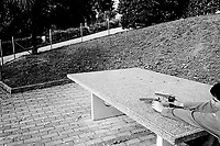 Switzerland. Canton Ticino. Viganello. A boy plays with two plastic toy guns in a public park. Concrete ping pong table. Viganello is 5 km distant from Lugano.© 2002 Didier Ruef