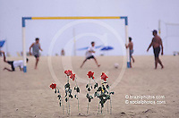 Rio de Janeiro, Brazil. New Year celebration at Copacabana beach. Afro-brazilian religious rituals ( Umbanda ). Religion, red roses in the beach sand. Offerings to Iemanjá, the Sea Goddess. Beach soccer game in background.