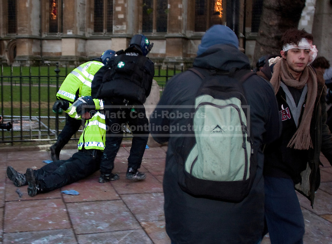 As an injured protester leaves a sterile area between police lines on Victoria Street, an unconscious policeman is attended to by colleagues. 09/12/10