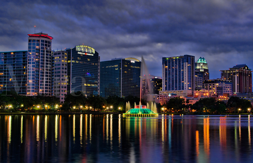 Orlando Florida Skyline and fountain at Lake Eola in early evening at sunset with reflections in the water