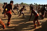 Lutadores de diversas aldeias se preparam para o Huka-huka.<br /> <br /> Huka-hukaLuta corporal que na terminologia kamaiurá lembra os gritos dos lutadores ao se defrontarem imitando o rugido da onça. Os anfitriões enfrentam uma aldeia convidada de cada vez, começando por lutas individuais de campeões reconhecidos. Seguem-se lutas simultâneas de vários pares de rivais, até as lutas dos muito jovens. Os lutadores se defrontam batendo o pé direito no chão, dando voltas no sentido dos ponteiros do relógio, com o braço esquerdo estendido e o direito retraído, enquanto gritam alternadamente: hu! ha! hu! ha! Até que chocam as mãos direitas e enlaçam o pescoço do adversário com a esquerda. A luta, que pode durar poucos segundos, termina quando um dos adversários é derrubado, o que não tem que ocorrer literalmente, bastando que a parte posterior de um de seus joelhos seja agarrada pela mão do outro, o que é considerado condição suficiente para provocar-lhe a queda. As aldeias convidadas não lutam entre si. Os enfeites dos troncos do Kwarup podem ser dados aos lutadores vencedores e também aos dois tocadores de maracá..<br /> Querência, Mato Grosso, Brasil. <br /> Foto Paulo Santos<br /> 26/07/2015