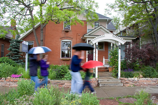 Family with umbrellas passing a Victorian style home near the Pearl Street Mall in Boulder, Colorado, USA .  John leads private photo tours in Boulder and throughout Colorado. Year-round.