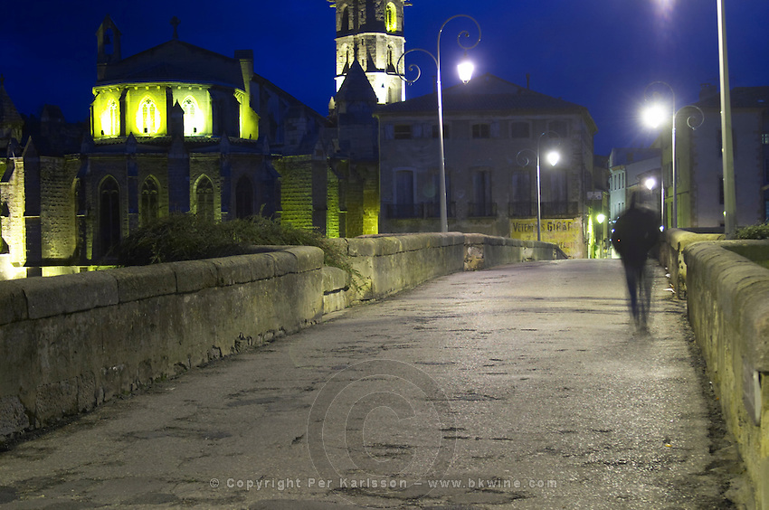 the bridge across the l'Aude river with a man walking across the bridge. Motion blur. Town of Limoux. Limoux. Languedoc. Illuminated at evening time and night. France. Europe.