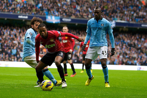 09.12.2012 Manchester, England. Manchester United's French defender Patrice Evra, Manchester City's Spanish midfielder David Silva and Manchester City's Italian forward Mario Balotelli in action during the Premier League game between Manchester City and Manchester United from the Etihad Stadium. Manchester United scored a late winner to take the game 2-3.
