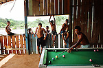 Boys play pool in a village bar in a clearing in the rainforest. The Floresta Nacional do Tapajos (FLONA), a 6500 km2 protected reserve, was home to several small communities which lived on the banks of the Rio Tapajos river. Most communities did not have electricity or running water and access to the villages was by unpaved dirt roads from Santarem and Highway BR163.