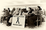 "May 9, 2011 - MINEOLA, NY:  Amid adults at public hearing, young Ramel Smith, Jr., sitting with sign: ""We Mourn the Death of Civil Rights in Nassau County."" Front row, first left is Golena White of Hemptead. Nassau County Legislature's public hearing on Legislative Redistricting, at Nassau County Executive and Legislative Building, 1550 Franklin Avenue, Mineola, Long Island, New York, USA."