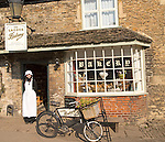 Young shopkeeper woman in old fashioned traditional clothing outside the village bakery shop, Lacock, Wiltshire, England, UK