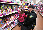 CCSO Dep. Dan Jones helps a young shopper pick a doll at the 10th annual Holiday with a Hero event at Walmart in Carson City, Nev., on Wednesday, Dec. 17, 2014. The event pairs 200 of Carson City's K-5th grade homeless students with a local heroes for Christmas shopping. <br />