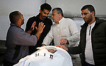 """Relatives mourn over the body of a Palestinian fisherman Ismail Abu Riala, 18, who was shot dead by Israeli Naval forces on February 14, after Israeli High Court decided to release his body at al-Shifa hospital, in Gaza City on March 14, 2018. A spokeswoman for the Israeli army said the boat """"deviated from the designated fishing zone in the northern Gaza Strip. """"Naval forces called on the boat to halt, then fired warning shots in the air before shooting toward it when the three people on board did not stop, the spokeswoman said. Photo by Ashraf Amra"""