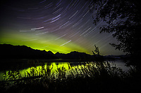 Fall landscape of the Northern Lights (Aurora Borealis) appearing in the night sky with star trails streaking across the sky.  Knik River with the Chugach Mountains in the background.  Matanuska Valley, near Palmer Alaska  Southcentral.<br /> <br /> Photo by Jeff Schultz/SchultzPhoto.com  (C) 2016  ALL RIGHTS RESVERVED