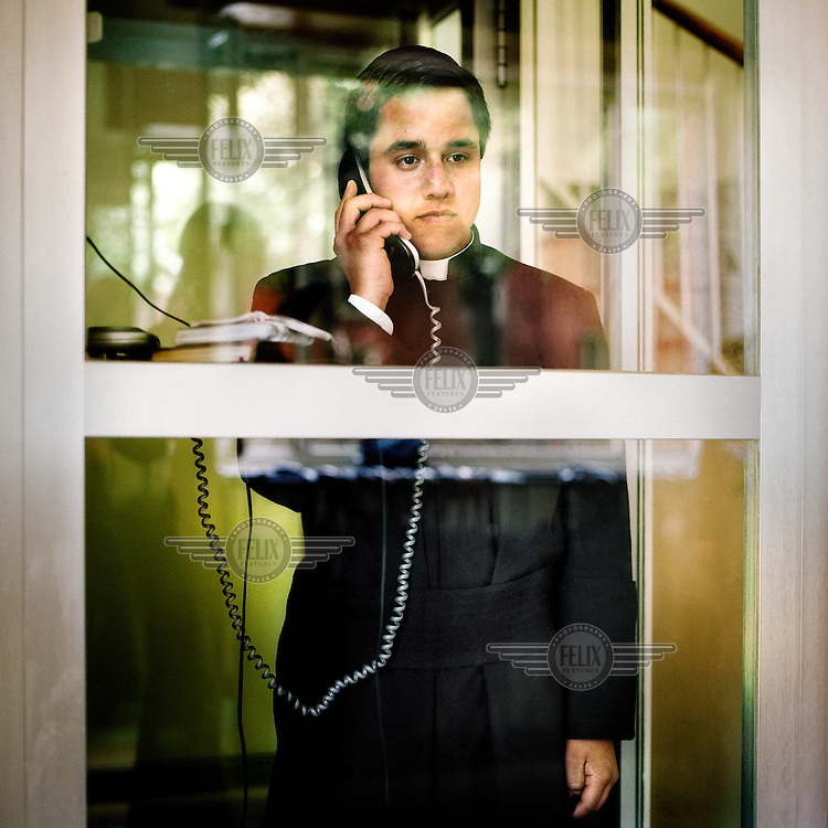 A young priest talks on a telephone at the Legionaries of Christ seminary in Salamanca. Seminarians' contact with their families is limited to once a month. Direct contact is always at the mercy of their superior. The Legion of Christ is a conservative Roman Catholic congregation whose members take vows of chastity, obedience and poverty.
