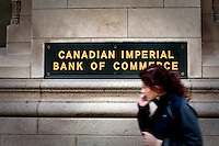 A woman talking on her cell phone walks by a Canadian Imperial Bank of Commerce office in Toronto financial district April 19, 2010. The Canadian Imperial Bank of Commerce (in French, Banque Canadienne Imperiale de Commerce, and commonly CIBC in either language) is one of Canada's chartered banks, fifth largest by deposits.