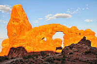Visitors watch sunrise highlighting sandstone Turret Arch in Arches National Park, Moab, Utah.