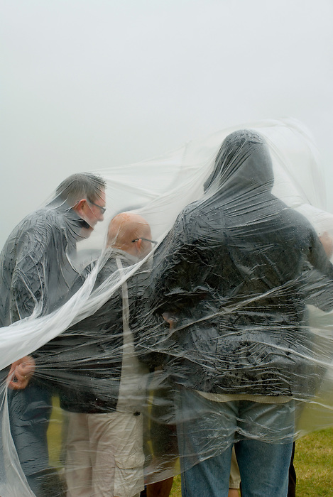 Festival goers shelter under plastic sheeting at Hop Farm one day festival, July 6 2008.