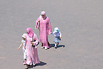 Two women with their daughters walk down a street in Marrakesh, Morocco.