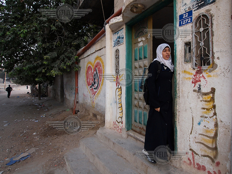 """Amira Al-Qerem (16) waits for the school bus at her new home in Gaza City on October 27 2010. Amira was missing and presumed dead after she was injured by one of the same explosions that killed her father, brother and sister during the last days of the Israeli invasion of Gaza in 2009. She was found three days later, after her family thought they had buried her remains with those of the other three. She is one of the main subjects of the controversial documentary film """"Tears of Gaza"""" by director Vibeke Løkkeberg."""