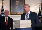 United States President Donald J. Trump walks past the large stack of papers that comprise the $1.3 trillion omnibus spending bill following his remarks after signing it at the White House in Washington, DC on Friday, March 23, 2018.  The President praised the increased military spending but noted measure does not protect the DACA program recipients and does not adequately fund his border wall, which he says is vital to national security. US Vice President Mike Pence looks on from left.<br /> Credit: Ron Sachs / Pool via CNP
