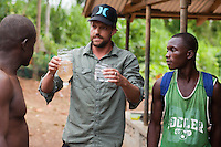 "Jon Rose works with Alphanso Appleton on a demonstration about using water filtration systems in Robertsport, Liberia. Rose holds ""before"" and ""after""  examples of local dirty water; on the right, the water after being filtered. One of the main strategies of Rose's organization, Waves 4 Water, is distributing filters to community leaders, then asking the communities to decide how the filters are to be used and shared. This grassroots, bottom-up process generates more inclusion and enthusiasm than an outsider giving orders."
