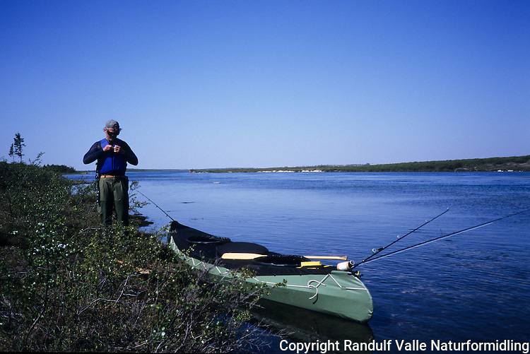 Mann og kano ved Thelon River, Canada. ---- Man and canoe beside Thelon River, Canada.