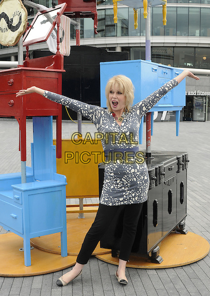 JOANNA LUMLEY  .The launch of the old furniture recycling scheme, The Scoop, More London, the Queen's Walk, London, England..July 12th, 2010.full length black grey gray white print top blue waist belt trousers leggings hands arms outstretched posing mouth open funny dresser chest of drawers.CAP/CAN.©Can Nguyen/Capital Pictures.