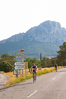 Mas de la Plaine, Mas Rigaud, Mas Bruguiere, Domaine de l'Hortus. A man on bicycle. The Pic St Loup mountain top peak. Pic St Loup. Languedoc. France. Europe.