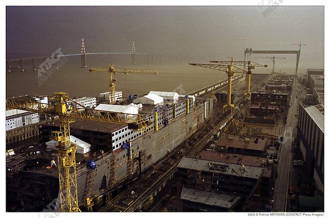 Construction of Queen Mary 2, Alstom Marine, Chantiers de l'Atlantique, Saint-Nazaire, France, December 2002. Saint Nazaire bridge in background