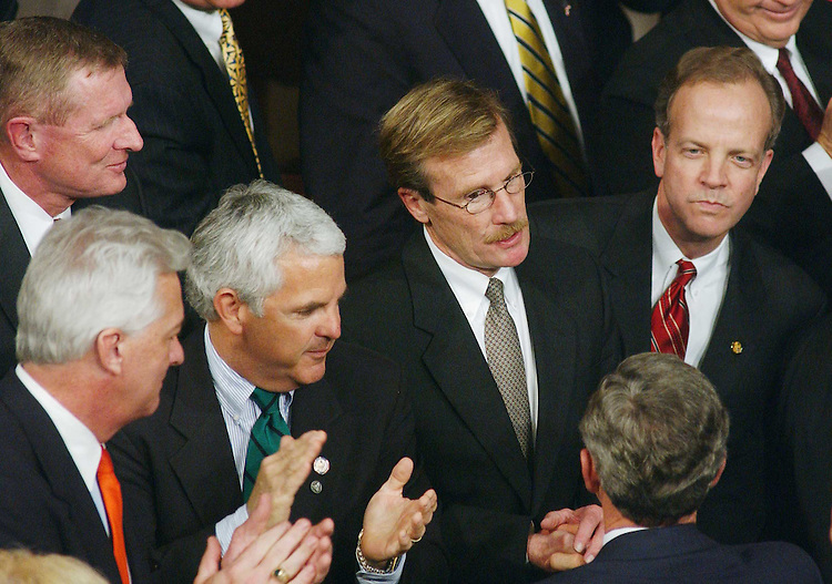 1/28/03.STATE OF THE UNION ADDRESS--As President George W. Bush leaves the chamber after delivering his State of the Union address, he is greeted by Jack Quinn, R-N.Y., John Shadegg, R-Ariz., Scott McInnis, R-Colo. (glasses and mustache), Jerry Moran, R-Kan., and Ed Schrock, R-Va. (behind Shadegg)..CONGRESSIONAL QUARTERLY PHOTO BY SCOTT J. FERRELL