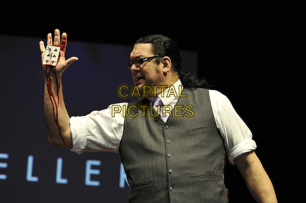 Penn Jillette .Penn and Teller performing 'Conversations with Penn and Teller - 35 Years of Magic and Bulls'%+t', indigo2, Greenwich, London, England. .7th December 2011.bullshit stage concert performing performance half length grey gray waistcoat white shirt pinstripe knife dagger hand profile card stab stabbing blood.CAP/MAR.© Martin Harris/Capital Pictures.