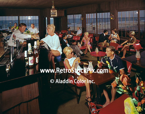 People in shorts and bathing suits having drinks at the Carousel Hotel bar in Ocean City, Maryland in the 1960's.