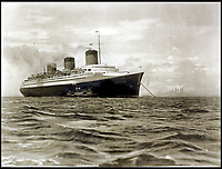 BNPS.co.uk (01202 558833)<br /> Pic:    CanterburyAuctionGalleries/BNPS<br /> <br /> The SS Normandie visited by a U.S. mail ship as she waits to enter New York harbour.<br /> <br /> Remarkable photos of the iconic ocean liner SS Normandie which was like a 'floating palace' have come to light over 80 years later.<br /> <br /> The giant 1,000ft long French passenger ship was the largest of her type in the world and won the coveted 'Blue Riband' for the fastest crossing of the Atlantic.<br /> <br /> English photographer Percy Byron's photos show the liner's luxurious 'Art Deco' interior with its chandeliers and pillars of Lalique glass.<br /> <br /> The vessel, which launched in 1935, even boasted its own swimming pool and a gym where young women can be seen doing aerobics while a man in a suit trains with a punch bag.