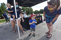 IF THE FIRE HAT FITS<br />Daniel Mann, 2, wears a souvenir fire hat on Saturday Aug. 1 2020 coutesy of Laura Butler (left) with the Beaver Lake Fire Department. The fire department and Benton County Sheriff's Office hosted a display of some of their vehicles and held a school-supplies drive at the Dollar General store in the Prairie Creek area. Visitors could purchase school suppllies in the store and donate them to the fire department, sheriff's office, or both, in a friendly competition to see which agency could collect the most school suppplies, said Jessika Buehne (cq), with the Beaver Lake Fire Department. Daniel was at the event with his mom, Elizabeth Mann (right). Butler holds her son, Lincoln Knyzewski (cq), 2. Go to nwaonline.com/200802Daily/ to see more photos.<br />(NWA Democrat-Gazette/Flip Putthoff)