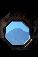 Agua Volcano framed by an octagonal window in the ruined Santa Clara Convent in the Spanish Colonial city of Antigua, Guatemala