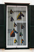 "Spain. Balearic Islands. Minorca (Menorca). Mahon.  Drawings of horses' heads used as decoration during the traditional summer festival of ""Festes de la Mare de Déu de Gràcia"". The Menorquín is a breed of horse indigenous to the island and is closely associated with the doma menorquina style of riding. The riders and their horses parade through the streets, and these magnificent and remarkably calm horses rear up on their hind-legs to the delight of the crowd. Some 150 riders participate in the festival in Mahón. Riders pass through the crowds, executing caracoles and repeatedly performing the bot. Maó (in Catalan) and Mahón (in Spanish), written in English as Mahon, is a municipality, the capital city of the island of Menorca, and seat of the Island Council of Menorca. The city is located on the eastern coast of the island, which is part of the autonomous community of the Balearic. In Spain, an autonomous community is a first-level political and administrative division, created in accordance with the Spanish constitution of 1978, with the aim of guaranteeing limited autonomy of the nationalities and regions that make up Spain. 7.09.2019 © 2019 Didier Ruef"
