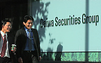 Businessmen pass through the sign of Daiwa securities Group, Tokyo, Japan..