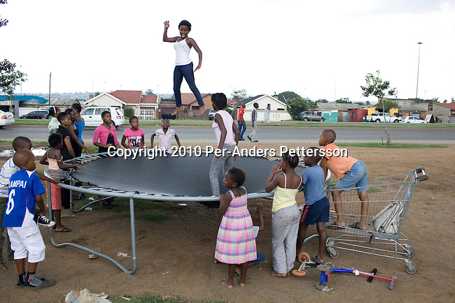 SOWETO, SOUTH AFRICA - JANUARY 17: Girls play on a trampoline on a street corner on January 17, 2010, in Soweto, South Africa. Soweto is the largest township in South Africa, located about 10 kilometers southwest of downtown Johannesburg. The population is estimated to be around 2-3 million. (Photo by Per-Anders Pettersson/Getty Images