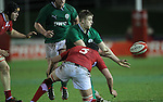 Ireland outside half Steve Crosbie gets his pass away as Wales lock Rhodri Hughes closes in..Under 20 Six Nations.Wales v Ireland.Eirias - Colwyn Bay.01.02.13.©Steve Pope