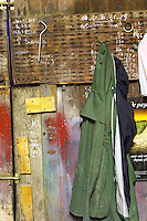 Domaine Terres Georges. In Castelnau d'Aude. Minervois. Languedoc. France. Europe. Tools and rain coats hanging on nails on the wooden cellar door.