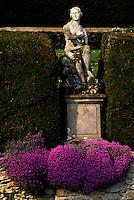 A statue of Venus sits comfortably above a vibrant cushion of purple aubretia.