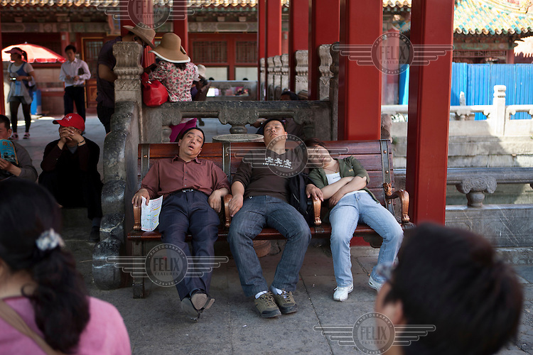 People sleep on a bench during a visit to the The Forbidden City. This was the Chinese Imperial Palace from the Ming Dynasty (1368 to 1644) to the end of the Qing Dynasty (1644 to 1912).
