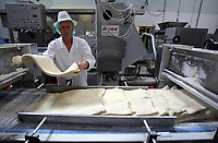 Pictured: A worker lifts pastry in one of the factory lines. Friday 26 May 2017<br /> Re: Lewis Pie and Pasty Company which has gone into halal products in Swansea, Wales, UK