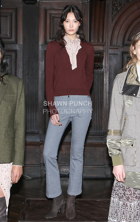 """Model Sun poses in a grey stretch denim seamed kick flare and bordeaux cashmere trompe l'Oeil tie neck sweater, from the Veronica Beard Fall 2016 """"Gypsy Caravan"""" collection presentation, at the Highline Hotel on February 15 2016, during New York Fashion Week Fall 2016."""