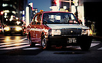 A Toyota Crown Super Deluxe makes a left turn into the posh Ginza district of Tokyo.