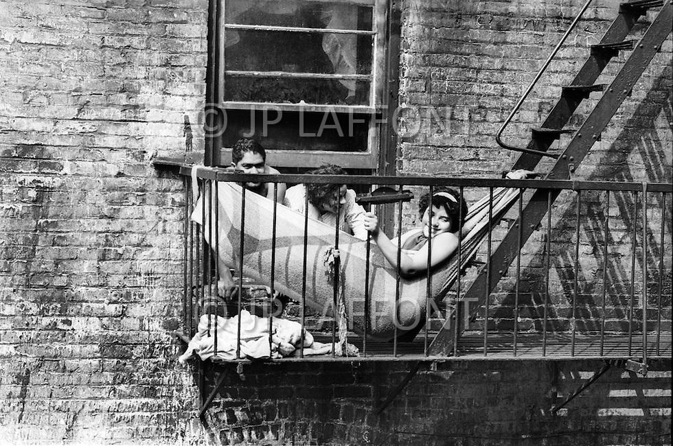 Bronx, New York City, NY - Summer of 1966<br /> A woman lounges in a hammock on the fire escape of her apartment building.  For tenants unable to afford the luxury of air conditioning, this was one way to escape the sweltering heat of their cramped apartments, and listen to salsa music.<br /> Bronx, New York City, NY. Et&eacute; 1966.<br /> Une femme dans son hamac cherche une fraicheur relative dans l&rsquo;escalier de secours de son building. Les cours int&eacute;rieures sont aussi les endroits o&ugrave; l&rsquo;on communique avec ses voisins, on se repose et on &eacute;coute de la musique salsa. Sc&egrave;ne touchante montrant une vie chaleureuse dans ce d&eacute;cor si dur.