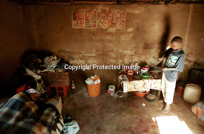 Domfikile Tibe and her son Spamale in their home on July 2, 2001 in Murchison, a rural area in Natal, South Africa. Domfikile is suffering from an Aids related disease and is mostly staying in bed. A hospice called South Coast Hospice visits patients in their homes and give them counseling and emotional support. South Africa has the highest infection rate in the world with about about 4.5 million people infected by HIV-Aids..Photo: Per-Anders Pettersson/ iAfrika Photos